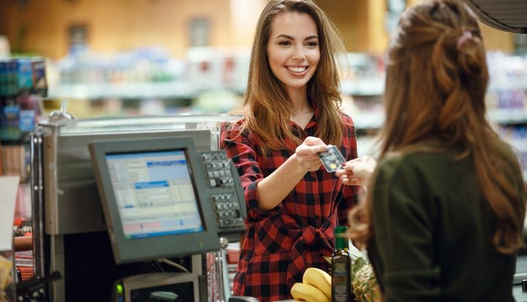 Young lady smiling at and handing her credit card to the cashier who standing behind a counter in a convenience store