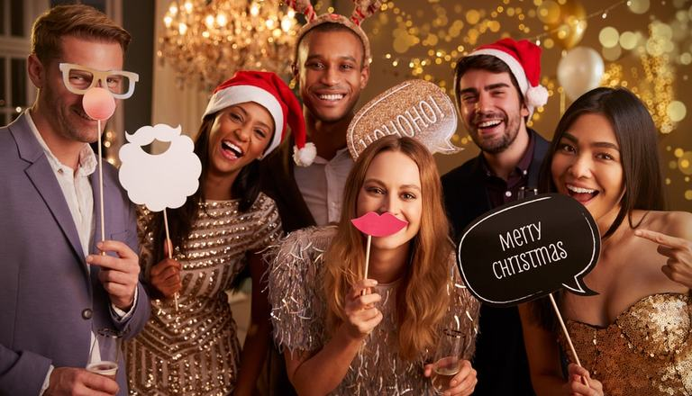 Group of adults celebrating Christmas with festive hats and signs