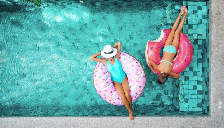 A bird's-eye view of two women lying in donut-style inflatable rings in a swimming pool